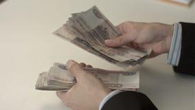El hombre de negocios cuenta el dinero en manos metrajes