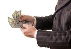 El hombre de negocios cuenta varios cientos de dólares aislados en blanco Imagen de archivo