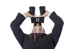 El hombre de negocios curioso sostiene los prismáticos hasta el cielo Fotos de archivo libres de regalías