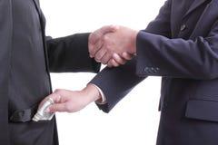 El hombre de negocios da a dinero para la corrupción algo Foto de archivo libre de regalías