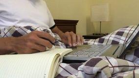 El hombre de negocios da el trabajo en el ordenador portátil que mecanografía haciendo la pluma de la escritura de la nota almacen de metraje de vídeo