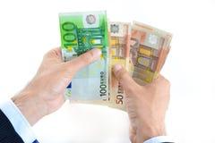El hombre de negocios da la cuenta del dinero, moneda euro (el EUR) Imagenes de archivo