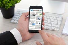 El hombre de negocios da sostener el teléfono con el sitio de las noticias de mundo en la pantalla foto de archivo libre de regalías