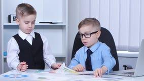 El hombre de negocios de dos niños pequeños en la oficina considera gráficos y cartas almacen de video