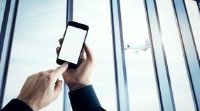 El hombre de negocios de la foto que sostiene smartphone moderno empuja el botón manualmente El blanco aislado de la pantalla en  fotos de archivo