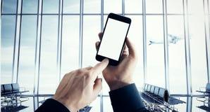 El hombre de negocios de la foto que sostiene smartphone moderno empuja el botón manualmente El blanco aislado de la pantalla en  foto de archivo