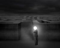 El hombre de negocios de pensamiento con la cabeza brillante de la lámpara iluminó el laberinto oscuro Fotografía de archivo libre de regalías