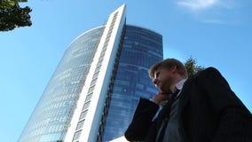 El hombre de negocios del agente de bolsa habla el teléfono del negocio, edificio de oficinas metrajes