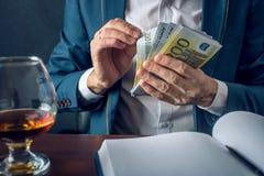 El hombre de negocios del hombre en traje pone el dinero en su bolsillo Un soborno bajo la forma de cuentas euro Concepto de corr Fotografía de archivo