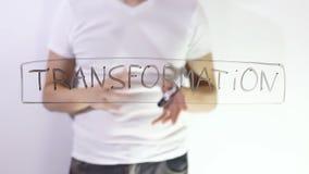 El hombre de negocios del hombre del texto de la inscripción de la transformación escribe en el vidrio metrajes