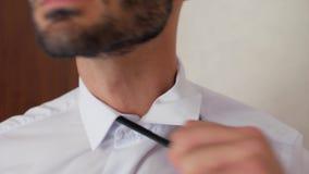 El hombre de negocios del individuo del primer con la barba en la camisa blanca saca el lazo negro El hombre saca su lazo 4K v?de almacen de metraje de vídeo