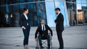 El hombre de negocios del lisiado en silla de ruedas y dos sus colegas tiene conversación positiva almacen de video