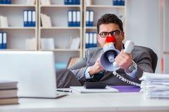 El hombre de negocios del payaso enojado en la oficina con un megáfono fotos de archivo libres de regalías