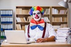 El hombre de negocios del payaso que trabaja en la oficina foto de archivo
