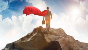 El hombre de negocios del super h?roe encima de la monta?a imágenes de archivo libres de regalías