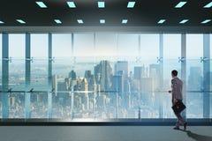 El hombre de negocios delante de la ventana de la oficina que piensa en nuevos desafíos Foto de archivo