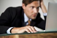 El hombre de negocios descansa su cabeza en una mano mientras que worki fotos de archivo libres de regalías