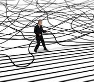 El hombre de negocios desenreda el cable Fotografía de archivo libre de regalías