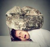 El hombre de negocios desesperado con la cabeza exprimió entre el ordenador portátil y la roca Imagenes de archivo