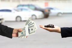 El hombre de negocios dio el dinero a la empresaria o a la dependienta que llevaba a cabo el modelo miniatura del coche, negocio  foto de archivo libre de regalías