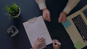El hombre de negocios disfruta en la firma de un contrato y sacude las manos con un socio que se sienta en la tabla Tiro de arrib almacen de video