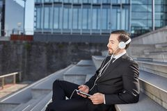 El hombre de negocios disfruta de música en una rotura foto de archivo