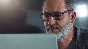 El hombre de negocios elegante casual trabaja con el ordenador portátil en su oficina almacen de video