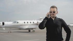 El hombre de negocios elegante en vidrios habla en el teléfono en el aeropuerto almacen de metraje de vídeo