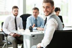 El hombre de negocios elegante feliz con el equipo acopla la discusión en el fondo foto de archivo