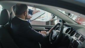 El hombre de negocios elegante firma el conract del auto de compra en concesión de coche almacen de metraje de vídeo