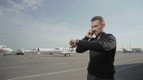 El hombre de negocios elegante habla en el teléfono en el fondo de aviones almacen de video