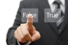 El hombre de negocios elige el botón virtual con la palabra falsa en lugar de otro verdad Imagenes de archivo