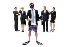 El hombre de negocios en aletas y gafas se opone al grupo de encargados imagen de archivo
