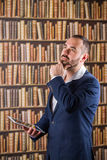 El hombre de negocios en biblioteca piensa con una tableta en manos Imágenes de archivo libres de regalías