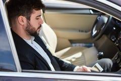 El hombre de negocios en el coche está leyendo un mensaje de texto imagenes de archivo
