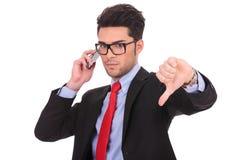 El hombre de negocios en el teléfono muestra el pulgar abajo fotografía de archivo