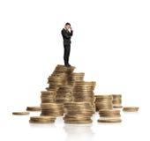 El hombre de negocios en el traje negro que se colocaba en el montón de monedas de oro que brillaban aisló el fondo blanco Fotos de archivo libres de regalías