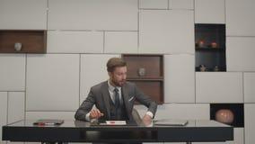 El hombre de negocios en extremos elegantes del traje trabaja llamada de teléfono en su gabinete, se sienta en su tabla de la ofi almacen de video