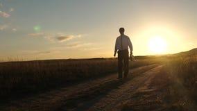 El hombre de negocios en gafas de sol va abajo de la carretera nacional con una cartera en su mano Concepto agr?cola del negocio  almacen de video