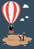 El hombre de negocios en globo del aire caliente consigue lejos de la arena movediza Imagenes de archivo