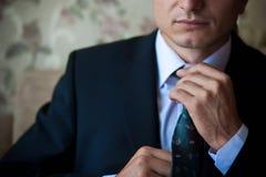 El hombre de negocios en juego ajusta su lazo Fotografía de archivo libre de regalías