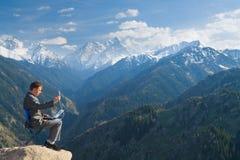 El hombre de negocios en la cima de la montaña usando networ inalámbrico Fotos de archivo libres de regalías