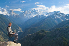 El hombre de negocios en la cima de la montaña usando su ordenador portátil Foto de archivo