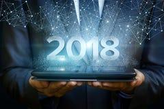 El hombre de negocios en la tableta muestra los números 2018 Imágenes de archivo libres de regalías