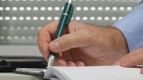 El hombre de negocios en oficina escribe en calendario del orden del día y base de datos del ordenador portátil del uso almacen de metraje de vídeo
