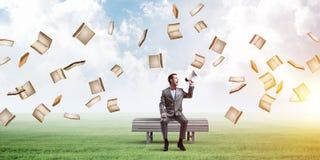 El hombre de negocios en parque del verano que anuncia algo en altavoz y los libros vuelan alrededor Imágenes de archivo libres de regalías