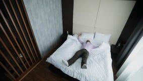 El hombre de negocios en ropa de la oficina está bajando en la cama en una habitación almacen de video