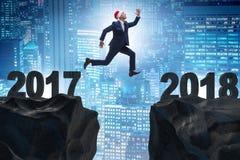 El hombre de negocios en el sombrero de santa que salta a partir de 2017 a 2018 Imágenes de archivo libres de regalías