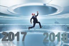 El hombre de negocios en el sombrero de santa que salta a partir de 2017 a 2018 Foto de archivo libre de regalías