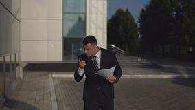 El hombre de negocios en traje negro que habla en smartphone y rechaza documentos contra el fondo del edificio del negocio al air metrajes